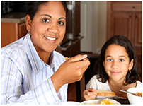 Image of mother and daughter eating  a healthy breakfast